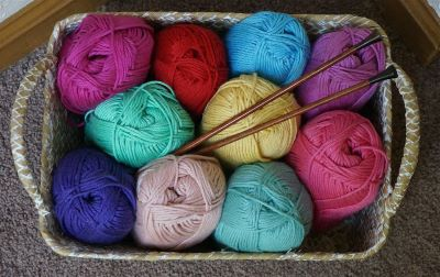 photo of colorful balls of yarn with knitting needles