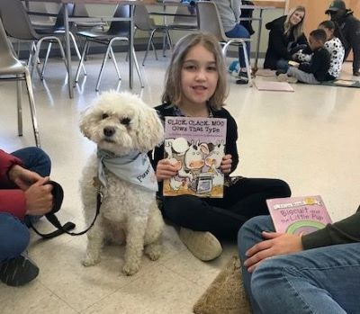 child holding book with therapy dog