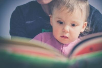Photo of a toddler reading a book with caregiver